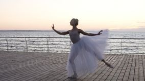 Young beautiful ballerina dressed in white tutu dancing gracefully on her pointe ballet shoes. Jumping, performing