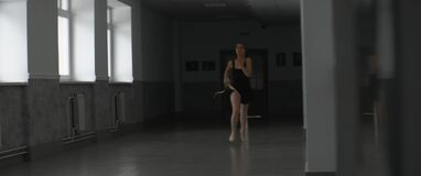 Young ballerina hurry to rehearsal or performance, running down the hall