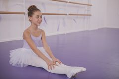 Charming young girl ballerina exercising at dance school royalty free stock image