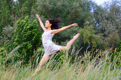 Young beautiful ballerina jumping high in the air on sunny summe Royalty Free Stock Image