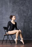 Young and beautiful ballerina sitting on a chair in a point shoes Royalty Free Stock Image