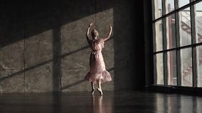 A young beautiful ballerina is spinning on her toes in pointes and dancing a classical ballet on a dark background. slow stock footage