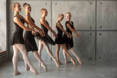 Women dance balet. Young beautiful ballerinas in black dresses, young pantyhose and pointe shoes stand in one row and dance a ballet in the form of a black swan royalty free stock images
