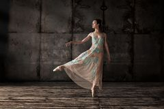 Young beautiful ballet dancer in beige dress stock photography