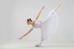 Young and beautiful ballet dancer posing isolated. Full length portrait of young and beautiful modern style ballet dancer taking classical ballet poses, lifting Stock Image