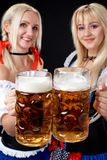 Young and beautiful bavarian girls with two beer mugs on black background stock photos