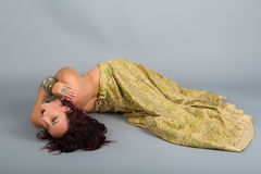 Young beautiful belly dancer in a golden costume royalty free stock photo
