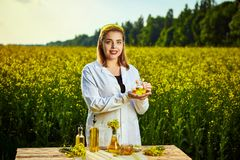 A young beautiful biologist or agronomist examines the quality of rapeseed oil on a rape field. Agribusiness concept. A young beautiful biologist or agronomist royalty free stock images