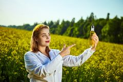 A young beautiful biologist or agronomist examines the quality of rapeseed oil on a rape field. Agribusiness concept. A young beautiful biologist or agronomist royalty free stock photo