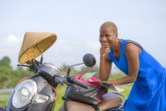 Young beautiful black afro american tourist woman with scooter motorbike looking to road map searching the way exploring fields in Stock Images