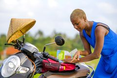 Young beautiful black afro american tourist woman with scooter motorbike looking to road map searching the way exploring fields in stock photo