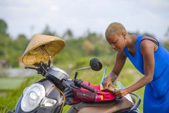 Young beautiful black afro american tourist woman with scooter motorbike looking to road map searching the way exploring fields in Royalty Free Stock Photo