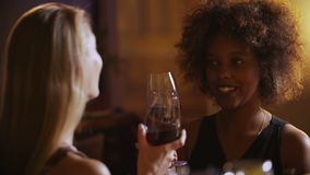 Young beautiful black and blonde girls drinking red wine at the luxury bar.  stock video footage
