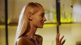Young beautiful black and blonde girls drinking red wine at the luxury bar. Foreground clear wine glass.  stock video