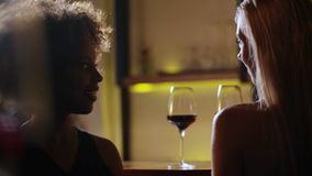 Young beautiful black and blonde girls drinking red wine at the luxury bar. Foreground clear wine glass.  stock footage