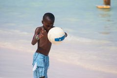 Young beautiful black boy  in blue shorts  playing football on the sunny caribbean beach just after swimming .Bavaro beach,Punta. Cana,Dominican Republic royalty free stock photo