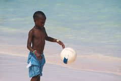 Young beautiful black boy  in blue shorts  playing football on the sunny caribbean beach just after swimming .Bavaro beach,Punta royalty free stock image