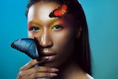 Young and beautiful black model exotic look with bright blue butterfly. Young and beautiful black model, exotic look with bright blue butterfly royalty free stock images