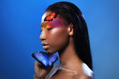Young beautiful afro girl, with two butterflies, beauty portrait on blue background. Young and beautiful black model, exotic look with bright blue butterfly Royalty Free Stock Photos