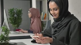 Young beautiful girl in black hijab sits in office and uses smartphone. Girl in black hijab in the background. Arab