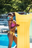 Young beautiful black woman posing with inflatable mattress at poolside royalty free stock photo