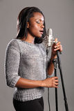 Young beautiful black woman singing in microphone stock photography