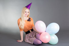 Young beautiful blond with balloons sitting over grey Royalty Free Stock Images