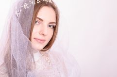 Young beautiful blond fiancee portrait with white veil. Young beautiful blond fiancee portrait with white veil on light background looking at camera smiling Royalty Free Stock Photos