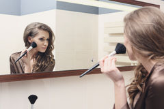 The young beautiful girl does makeup Stock Image