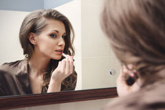 The young beautiful girl does makeup Stock Photography