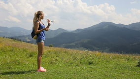 Young beautiful blond girl drinks water in the mountains.  stock footage