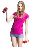 Young beautiful blond girl holding dumbbells Stock Images