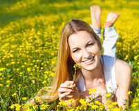 Young beautiful blond girl laying on the daisy flowers field. Ou Stock Photography