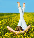 Young beautiful blond girl laying on the daisy flowers field Stock Photo