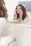 Young beautiful girl looks in the mirror Royalty Free Stock Images