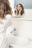 Young beautiful girl looks in the mirror Stock Photography