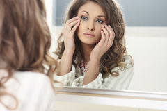 Young beautiful girl looks in the mirror Royalty Free Stock Photo