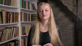 Young beautiful blond girl with pink lipstick is reading book, watching at camera, smiling, library on background.  stock video footage