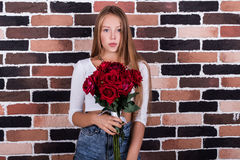 Young beautiful blond girl with red roses royalty free stock photo