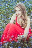 Young beautiful blond girl sitting in red dress in cornflower field Royalty Free Stock Photos