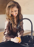 Young beautiful girl washes the orange Royalty Free Stock Photos