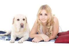 Young beautiful blond in pajamas lying with dog isolated on whit Stock Image