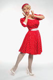 Young beautiful blond pin-up woman. Young beautiful blonde in red dress pin-up in the studio stock photography