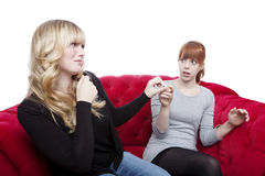 Young beautiful blond and red haired girls get cigarette away on Royalty Free Stock Photo