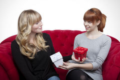 Young beautiful blond and red haired girls giving present box on Stock Photo