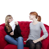 Young beautiful blond and red haired girls hide letter on red so. Fa in front of white background Royalty Free Stock Image