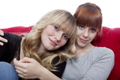 Young beautiful blond and red haired girls hug while sitting on Stock Photography