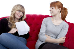Young beautiful blond and red haired girls open a letter on red. Sofa in front of white background Royalty Free Stock Images