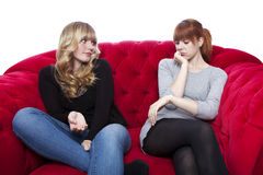 Young beautiful blond and red haired girls on red sofa are bored Royalty Free Stock Photos