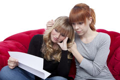 Young beautiful blond and red haired girls on red sofa are sad b Royalty Free Stock Photo